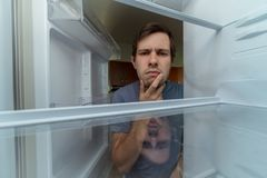 Hungry man is looking for food in empty fridge.  Royalty Free Stock Image