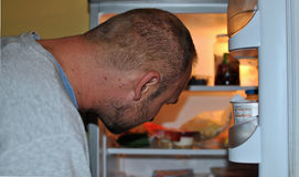 Hungry man. Looking for food in the fridge Royalty Free Stock Photos
