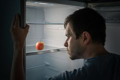 Hungry man is looking for food in fridge at night. Only apple is inside empty fridge Stock Photos