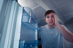 Hungry man looking in refrigerator. Portrait of a hungry man looking for food in refrigerator Royalty Free Stock Images