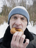 Hungry Man. Hungry matured man biting donut, outdoor vertical shot with blurred background Stock Photos