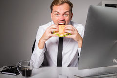 Hungry man at the office eating burger. Man at the office eating burger Royalty Free Stock Photography