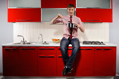 Hungry man. Portrait of  young hungry man filching  pan with soup on red kitchen Royalty Free Stock Image