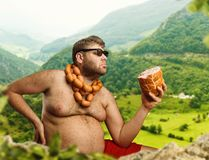 Hungry man with sausages. Round his neck eats one more sausage in the mountains Stock Image