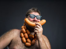 Hungry man with sausages. Round his neck eats one more sausage over grey Stock Images