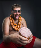 Hungry man with sausages Royalty Free Stock Image