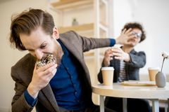 Hungry man taking doughnut out of woman royalty free stock image