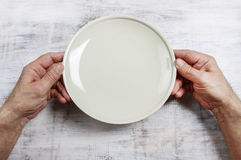 Hungry man waiting for his meal. Over empty plate on wooden table Stock Photography