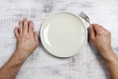 Hungry man waiting for his meal. Over empty plate on wooden table Royalty Free Stock Photos