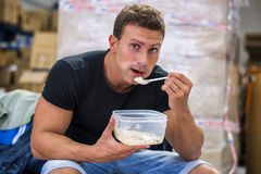 Hungry muscular shirtless man gulping down food Royalty Free Stock Image