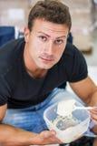 Hungry muscular shirtless man gulping down food Royalty Free Stock Photo
