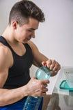 Hungry muscular young man gulping down food Stock Photos