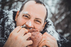 Hungry northern bearded eats meat. Survivor northern bearded man with a piece of meat. Portrait of a man with a beard devouring raw meat. Hungry northern Royalty Free Stock Images