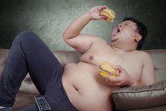 Hungry obese man eats two burgers. Picture of obese person looks hungry and eat two hamburger while leaning on the sofa Stock Photos