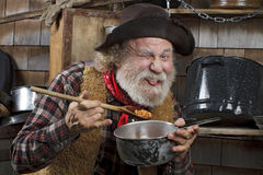 Hungry old cowboy eating beans from a saucepan Royalty Free Stock Images