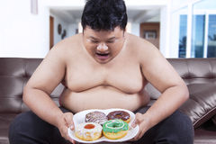 Hungry overweight man holding donuts Stock Images