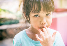 Hungry poor child licking her hand for the last test of her food. Royalty Free Stock Photo