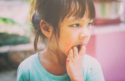 Hungry poor child licking her hand for the last test of her food. Royalty Free Stock Images