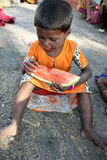 Hungry Poor Girl. A hungry beggar girl from India eating a watermelon, sitting on a street Stock Photos