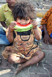 Hungry Poor Girl. A poor girl from India hungrily eating a watermelon Royalty Free Stock Image