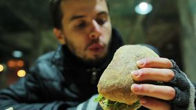 Hungry poor homeless man eating sandwich with vegetables at charity event. Stock footage stock video footage
