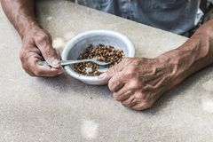Hungry. Poor old man& x27;s hands an bowl of porridge . Selective focus. Poverty in retirement. Alms, hunger, beggar, charity, despair, dining, eat, empty royalty free stock photography