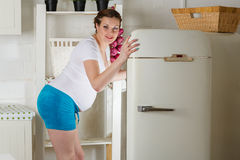 Hungry pregnant woman. Hungry young pregnant woman stands near refrigerator and searches the food Royalty Free Stock Photos