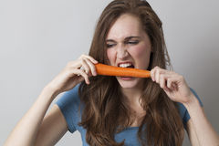 Hungry 20s girl biting a carrot with energy. Diet and food concept - young beautiful woman biting carrot with anger for frustrating diet stock photography