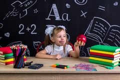 Hungry schoolgirl sitting at the desk with books, school supplies, holding in her arm red apple ready to bite stock photo