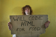 Hungry smiling programmer. Hungry programmer holding a cardboard with text Royalty Free Stock Images