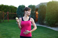Hungry sporty woman with apple Stock Photography