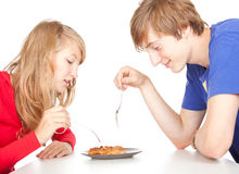 Hungry teenage couple eating pies Stock Photos