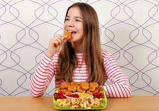 Hungry teenage girl eats chicken nuggets stock photos
