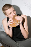 Hungry teenager. Sitting in the corner and eat bread Royalty Free Stock Image