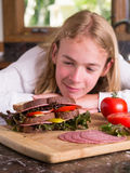 Hungry Teenager Looking at a Large Sandwich. A growing adolescent teenage boy with a big appetite looking forward to eating his latest sandwich creation Stock Photos