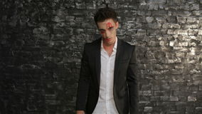 Hungry vampire pounced. Man in the image of the vampire posing on black background of a brick wall. Halloween concepts and costumes stock footage