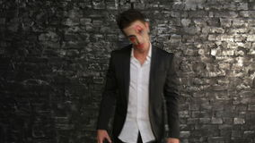 Hungry vampire saw the victim. Man in the image of the vampire posing on black background of a brick wall. Halloween concepts and costumes stock video