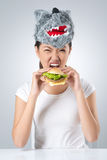 Hungry wolf. Vertical portrait of a carnivorous young woman wearing a wolf mask taking a bite of a hamburger Stock Image