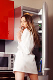 Hungry woman. Sexy, hungry woman near fridge royalty free stock photo