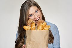 Hungry Woman bites bred from paper bag. Isolated female funny portrait Royalty Free Stock Photos