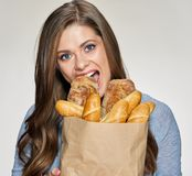 Hungry Woman bites bred from paper bag. Isolated female funny portrait Stock Photography