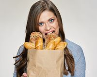 Hungry Woman bites bred from paper bag. Isolated female funny portrait Royalty Free Stock Images