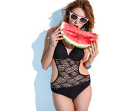 Hungry woman bites watermelon slice Stock Images