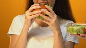 Hungry woman choosing fatty hamburger instead of green salad, risk of overweight