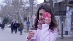 Hungry woman with cookie and tea in plastic cup on open air in city close-up. On an unfocused background stock video footage