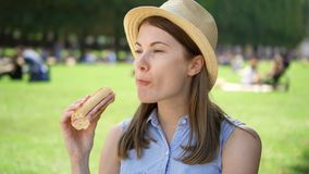 Hungry woman eating baguette in park. Tourist having lunch in public park enjoying summer sunny day stock footage