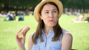 Hungry woman eating baguette in park. Tourist having lunch in public park enjoying summer sunny day stock video