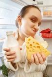 Hungry woman eating. Food near refrigerator looking at camera Stock Photos