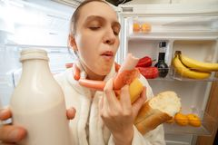 Hungry woman eating. Hungry fun woman eating food near refrigerator Royalty Free Stock Photo