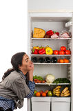 Hungry woman and a fridge full of food Stock Photography